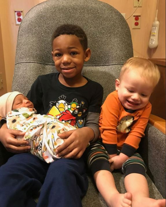 Milo Weight, 5 and his brother Nash Weight, 2, hold their baby sister Onni Weight, 3 months after her 2019 adoption in Utah.