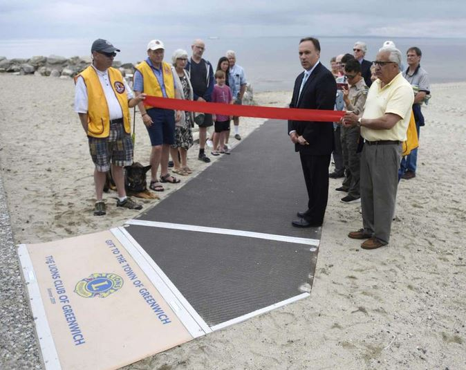 First Selectman Peter Tesei speaks before cutting the ribbon for the new ADA accessible ramp on the Greenwich Point Park beach in Old Greenwich, Conn.