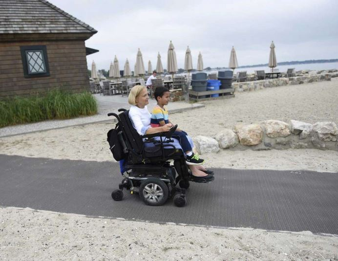 Greenwich residents Anne Hotchkiss and Angelo Arista, 5, use the new ADA accessible ramp on the Greenwich Point Park beach in Old Greenwich, Conn.