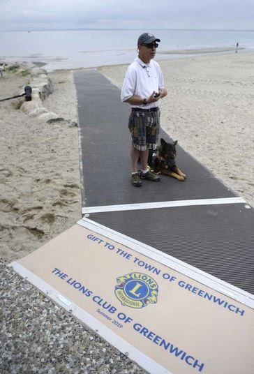 Alan Gunzburg, who serves on the First Selectman's Advisory Committee for People with Disabilities, stands on the new ADA accessible ramp on the Greenwich Point Park beach in Old Greenwich, Conn.