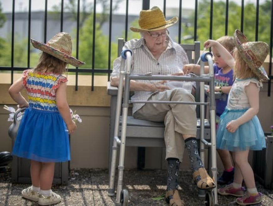 Children from the TowerLight Child Care Center helped Joan Johnson, from the TowerLight Memory Care Unit, water plants as part of their multigenerational program.