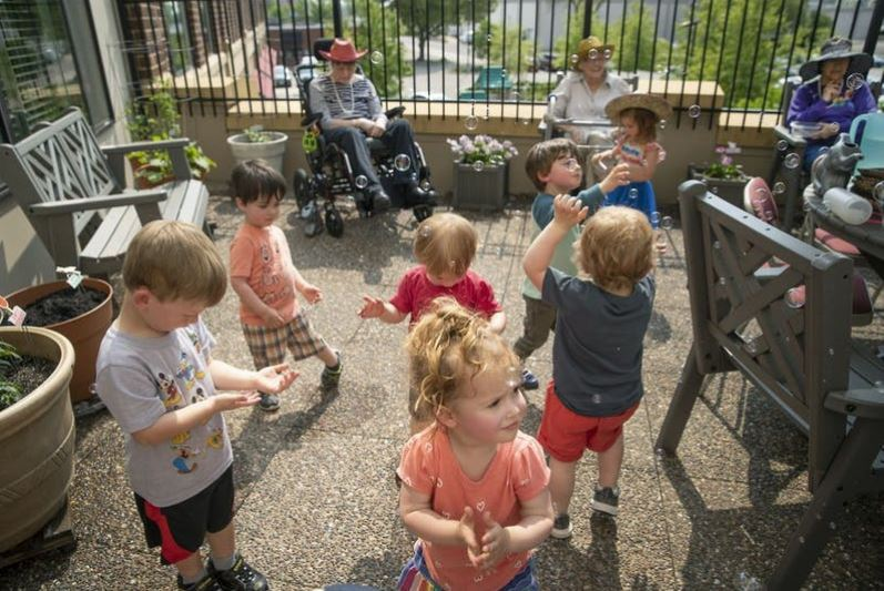 Children from the TowerLight Child Care Center played with bubbles as TowerLight Memory Care Unit residents watched after they watered plants as part of their multigenerational program.