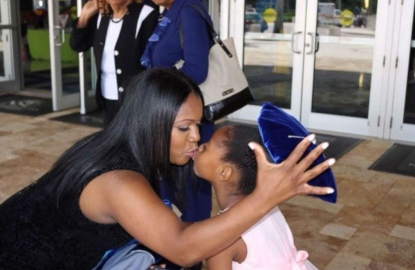 Yolanda Perkins kisses her daughter, Bella, 6, after Perkins' graduation ceremony on June 14.