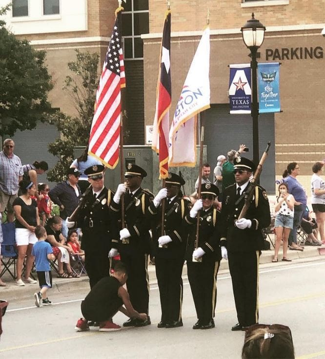 Joshua Brown ties Officer Jerrick Wilson's shoe during the annual Independence Day parade.