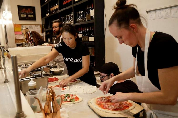 Mozzeria owner Melody Stein, left, and Sabrina Ferguson makes pizzas at the restaurant.