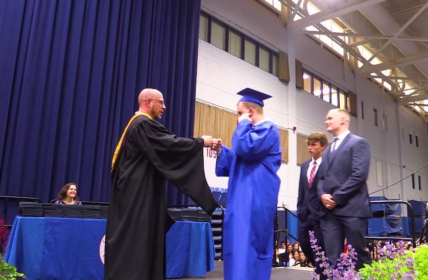 Jack Higgins was escorted to the stage then fist bumps to receive his diploma.