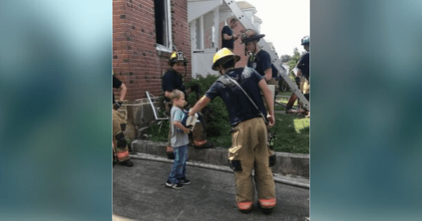 Boy hands out ice cream sandwiches to firefighters following a house fire battle.