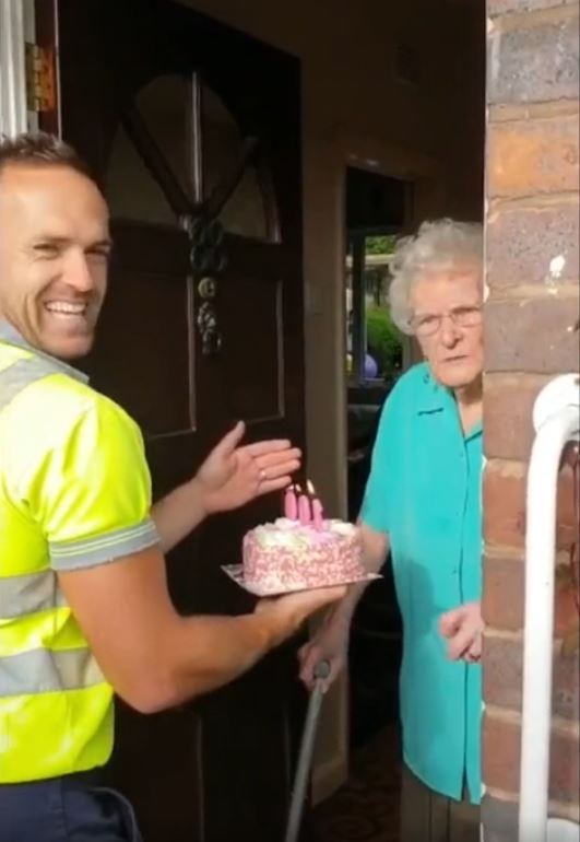 Garbage men surprise elderly woman on her 100th birthday with a cake and a little happiness. Credit: Ben Bird