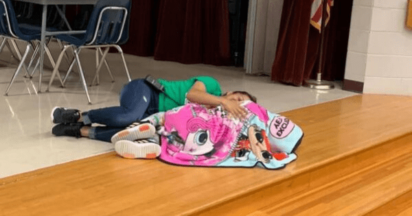 School custodian comforts little girl with autism by laying down next to her after she had a meltdown
