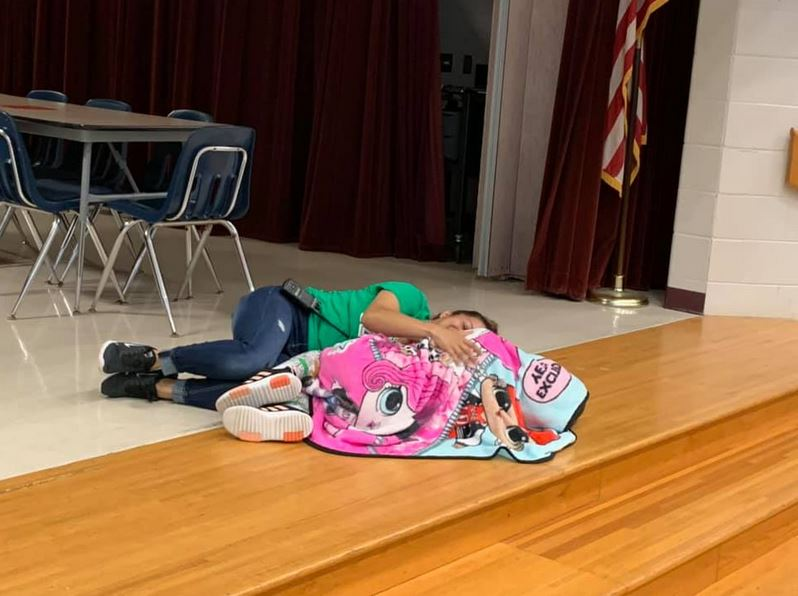 School custodian comforts little girl with autism by laying down next to her after she had a meltdown.