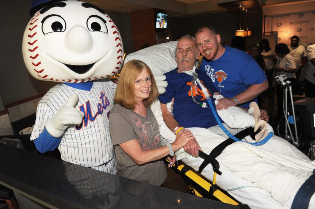 Nursing home patients who haven't left the facility in 3 years, attend baseball game.  McDermott family and Mr Met.