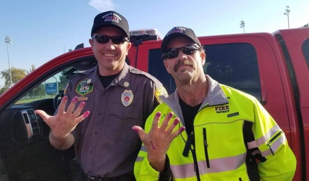 Firefighters calm scared little girl down after car crash by letting her paint their nails.