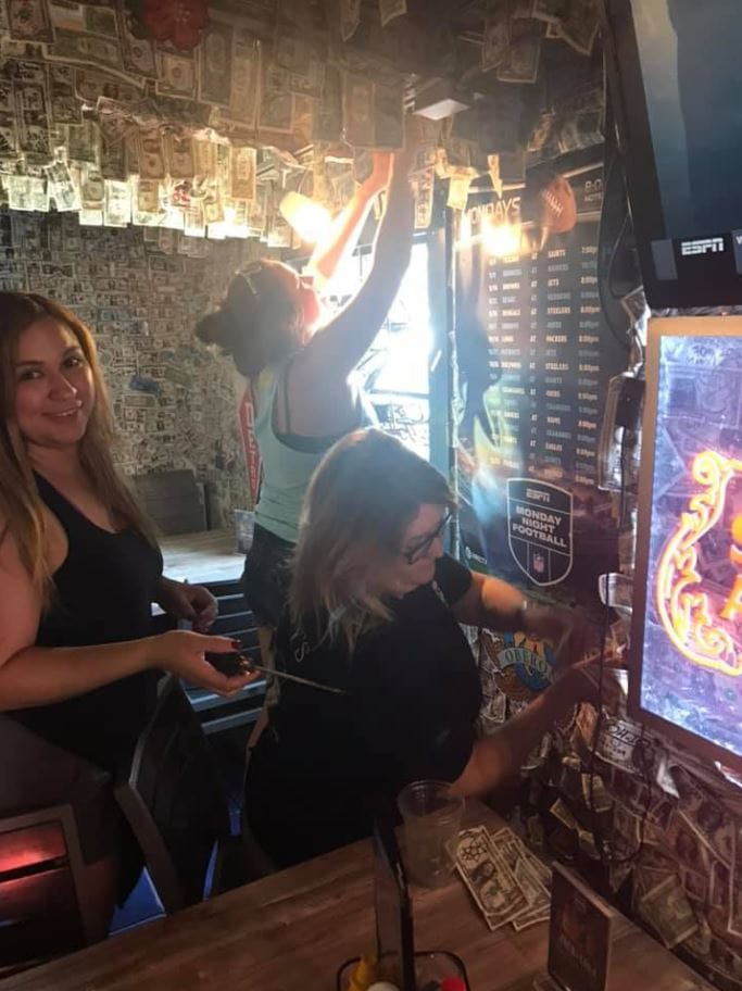 Florida bar collects over $15k for Bahamas Hurricane Dorian relief by taking down their dollar bill decor. Credit: Siesta Key Oyster Bar