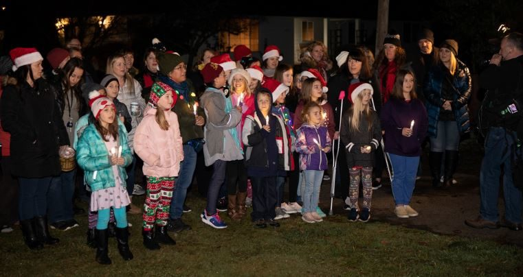 Students of beloved teacher fighting cancer show up on her front lawn to sing her Christmas carols.