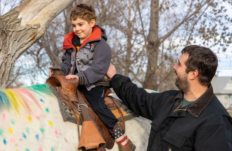"""Wyatt Haas slowly breaks into a smile as he sits up for his first """"unicorn ride"""" with dad, Zach Haas, watching."""