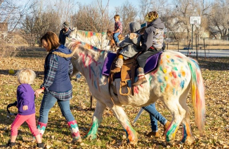 """Tamara Choat and Hunter Frost lead Lilly the """"unicorn"""" while Wyatt Haas and his sister, Aspen, take a ride."""