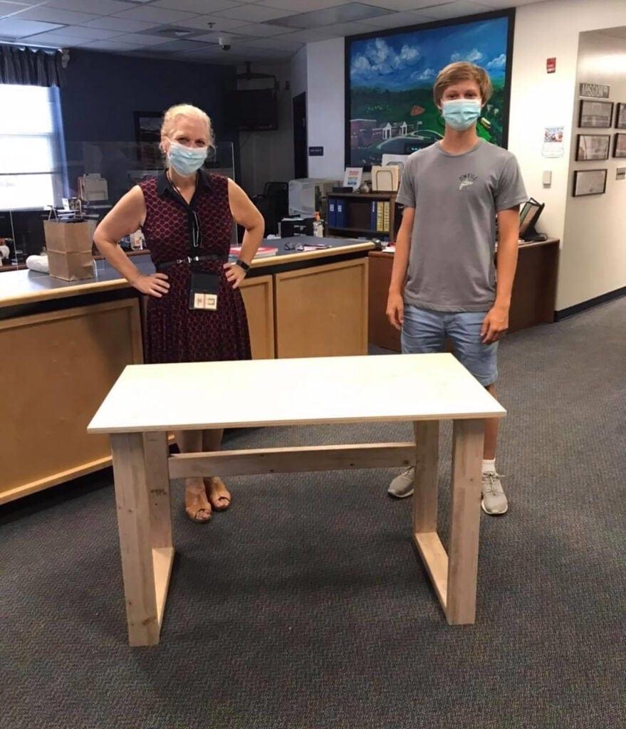 Teacher Kate Kurtzke and Colby Samide with her new desk he built.