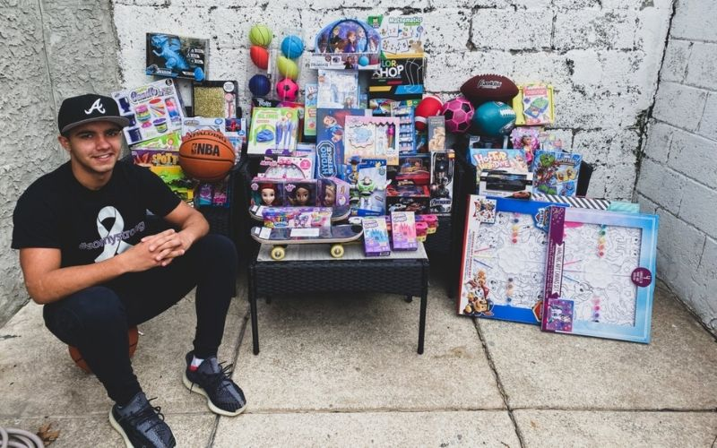 Angel Ortero sitting in front of the toys he bought to donate to kids in DR.